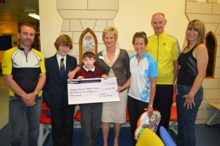 Kids from SPDC receiving a donation cheque from City and Sandwell Hospital's cyclists