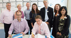 Front left Tony Waite, Finance Director and Toby Lewis, Chief Executive sign the contract in the presence of the SWBH NHS Trust Executive Team.