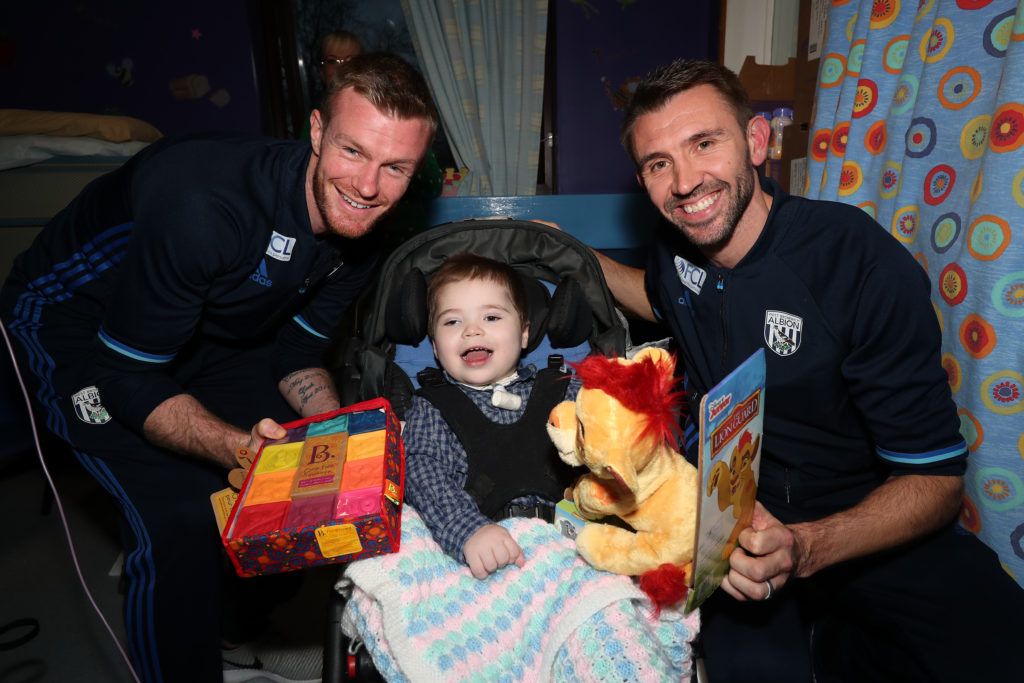 Chris Brunt of West Bromwich Albion and Gareth McAuley of West Bromwich Albion with Loki Hudson aged 3 at Sandwell Hospital where West Bromwich Albion players handed out Christmas presents  to sick children
